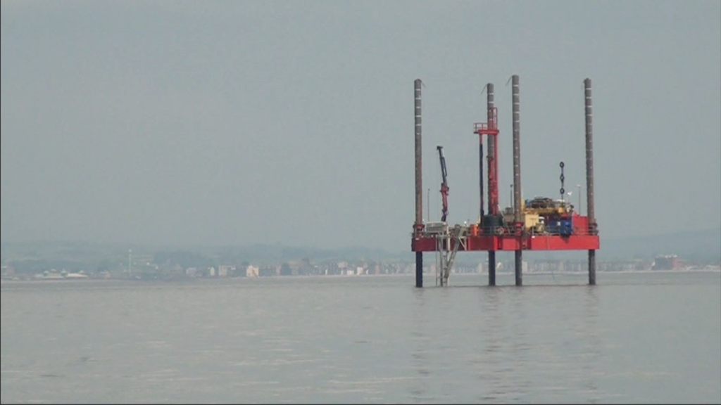 A prospecting drilling rig with the west end of Morecambe in the background